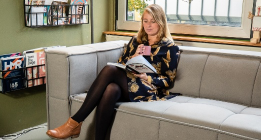 Vrouw die een boek leest op een bank